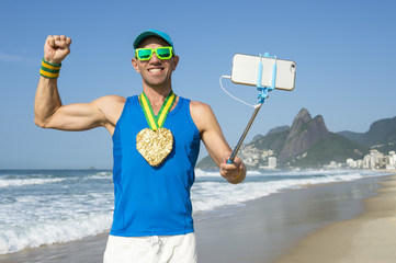 Athlete with heart shape gold medal posing for a celebratory selfie at Ipanema Beach, Rio de Janeiro, Brazil