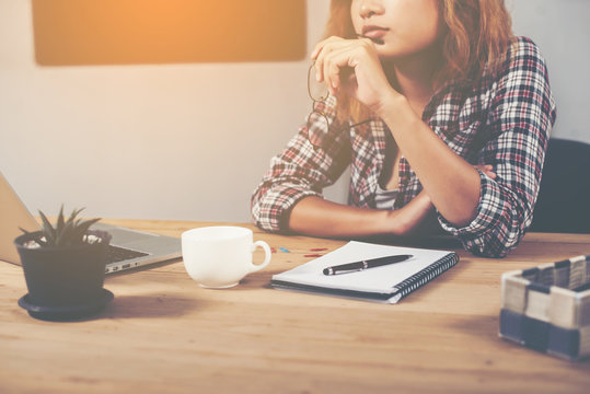 young beautiful hipster woman sitting on workplace and thinking