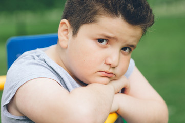 sad fat boy sitting on the sports simulator