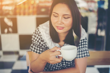 Young beautiful woman drinking coffee in a cafe.