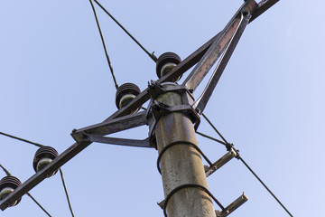 concrete pylon with the leadership of the voltage with the sky in the background