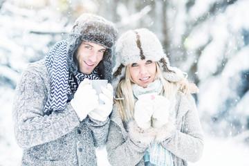 Pärchen mit Heißgetränk im Schnee