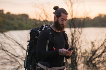 Bearded hiker checking cellphone near lake