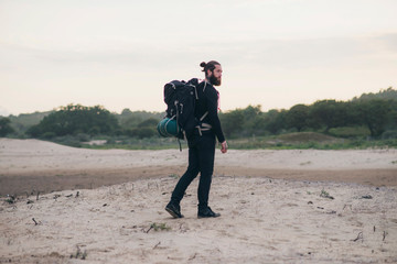 Man with backpack walking on sand dune landscape