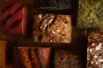 Many mixed alternative baked breads presented as samples for sale on rustic wooden table in professional bakery: pistachio,beetroot,tomatoes,lavender,sea salt, coal,sweet potato Close up