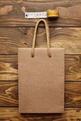 Brown takeaway bag from thic recycled craft paper on rustic wooden table near vintage tailoring meter mockup