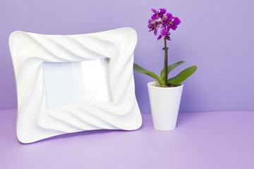 White photo frame and little orchid in purple