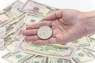 One silver dollar in her hand with hundreds and fifty banknotes as background