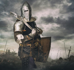 Knight in armour on battle rise under stormy sky.