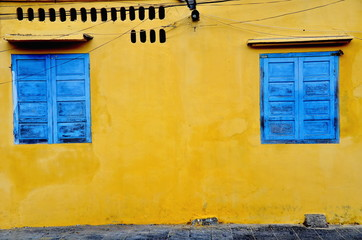 blue window and yellow wall at Hoi An in Vietnam