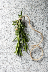 Green fresh rosemary on granite background