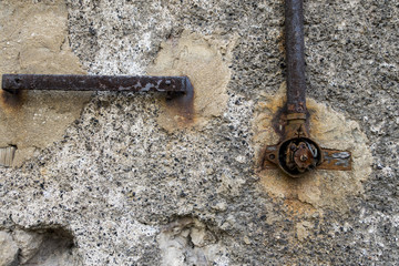 Remains of an old electrical installation mounted on a cracked wall.