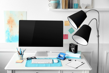 Modern wide screen monitor with lamp on white table in room interior