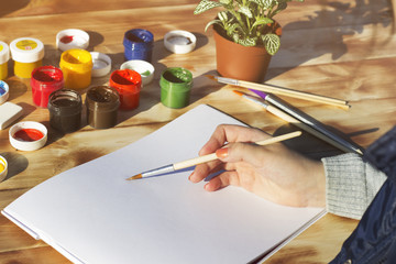 The artist's hand holds the brush and empty album, paint, pencils and flower on wooden background.