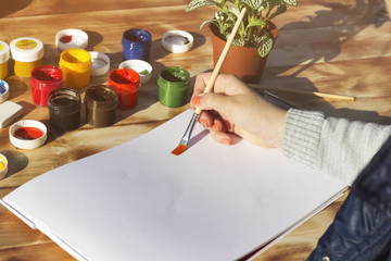 The artist's hand holds the brush and empty album, paint, pencils and flower on wooden background. The view from the top