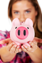 Smiling young woman holding piggybank