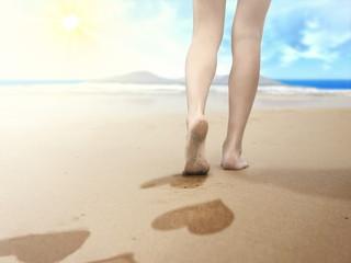 woman walking on seaside and leaving footprints
