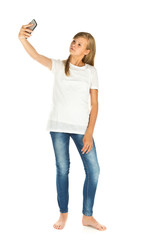 Young girl standing taking a selfie over white background