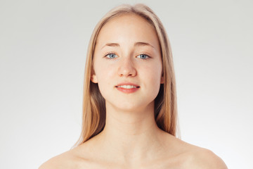 Beauty shoot of a young pretty girl nude. Blue eyes, blond hair, wearing no make-up in her perfect clear skin. Cosmetic advertisement style. Natural scandinavian face of a woman looking at the camera