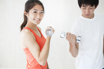 Young men and women are trained to arms dumbbell