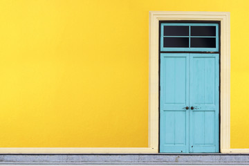 Closed blue wooden door on yellow wall background