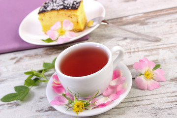 Cup of tea with cheesecake and wild rose flower on old wooden background