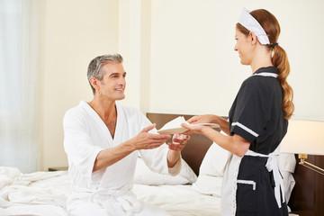 Zimmermädchen bringt Hausschuhe für Mann