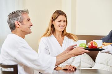 Zimmerservice bringt Paar Frühstück auf Tablett