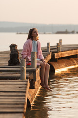 Young girl on pier  with dog in evening light