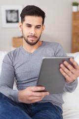 entspannter mann sitzt auf dem sofa und schaut auf tablet