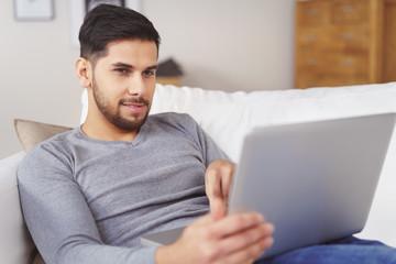 junger mann liegt gemütlich auf dem sofa und schaut auf laptop