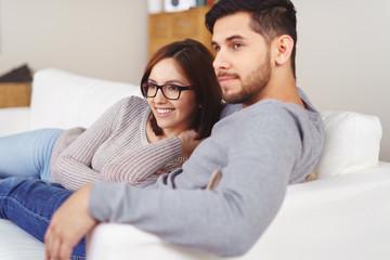 entspanntes paar liegt auf dem sofa und schaut sich etwas an