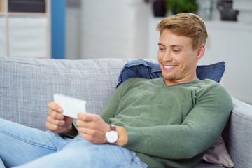 mann liegt auf der couch und schaut auf sein mobiltelefon