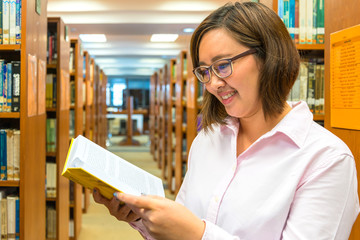 Portrait of a young student reading a book in a library