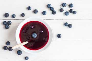 blueberry soup on wooden white background, top view, flat lay
