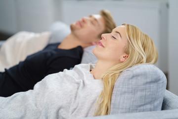paar liegt entspannt auf dem sofa mit geschlossenen augen