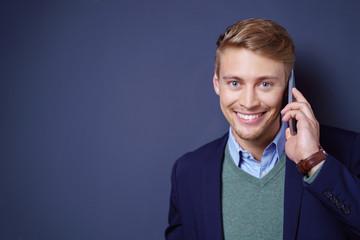 mann telefoniert mit seinem handy vor grauem hintergrund