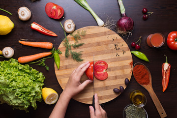 Photo from directly above of human hands cutting tomato on a cutting board and variation of vegetables and spices around prepared for recipe