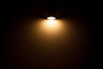 Wall lamp illuminated white wall with wallpaper