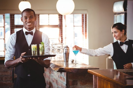 Mixed race bartender holding a serving tray with two cocktail glass