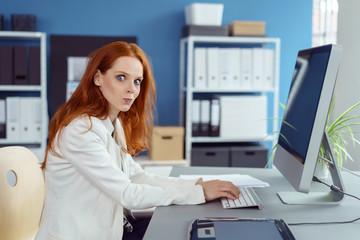 geschäftsfrau im büro macht große augen vor überraschung