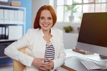 zufriedene geschäftsfrau sitzt am schreibtisch und lächelt