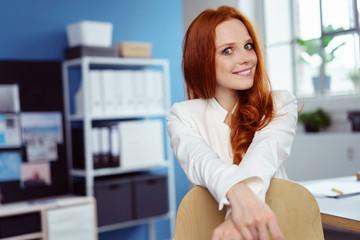 smarte junge frau sitzt am schreibtisch im büro