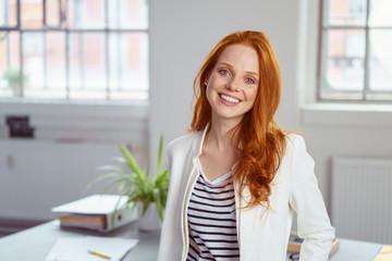 lächelnde geschäftsfrau steht in ihrem büro