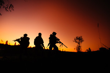 Silhouette of military soldiers with weapons at night. shot, hol
