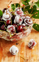 ripe cherries,ice cubes on wooden table, selective focus