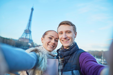 Happy couple of tourists taking selfie near the Eiffel tower
