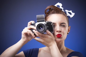 Pin Up girl taking photos with vintage camera