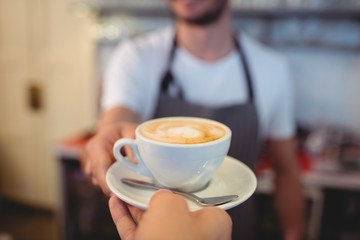 Cropped image of customer taking coffee from waiter at cafe