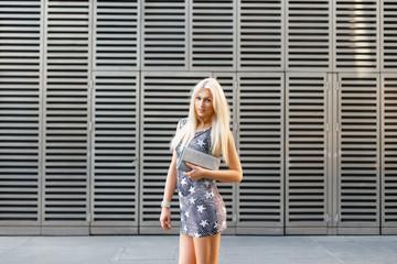 Stylish blond girl standing on a modern metallic background.